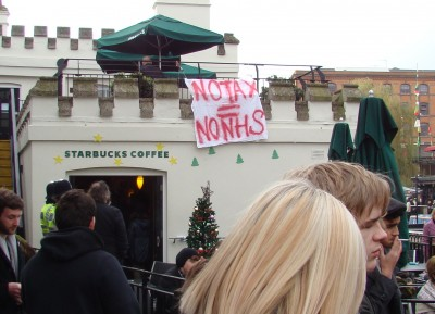 "A banner saying ""No tax = No NHS"" hung from Starbucks"